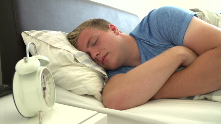 Teen boy waking up in a bed