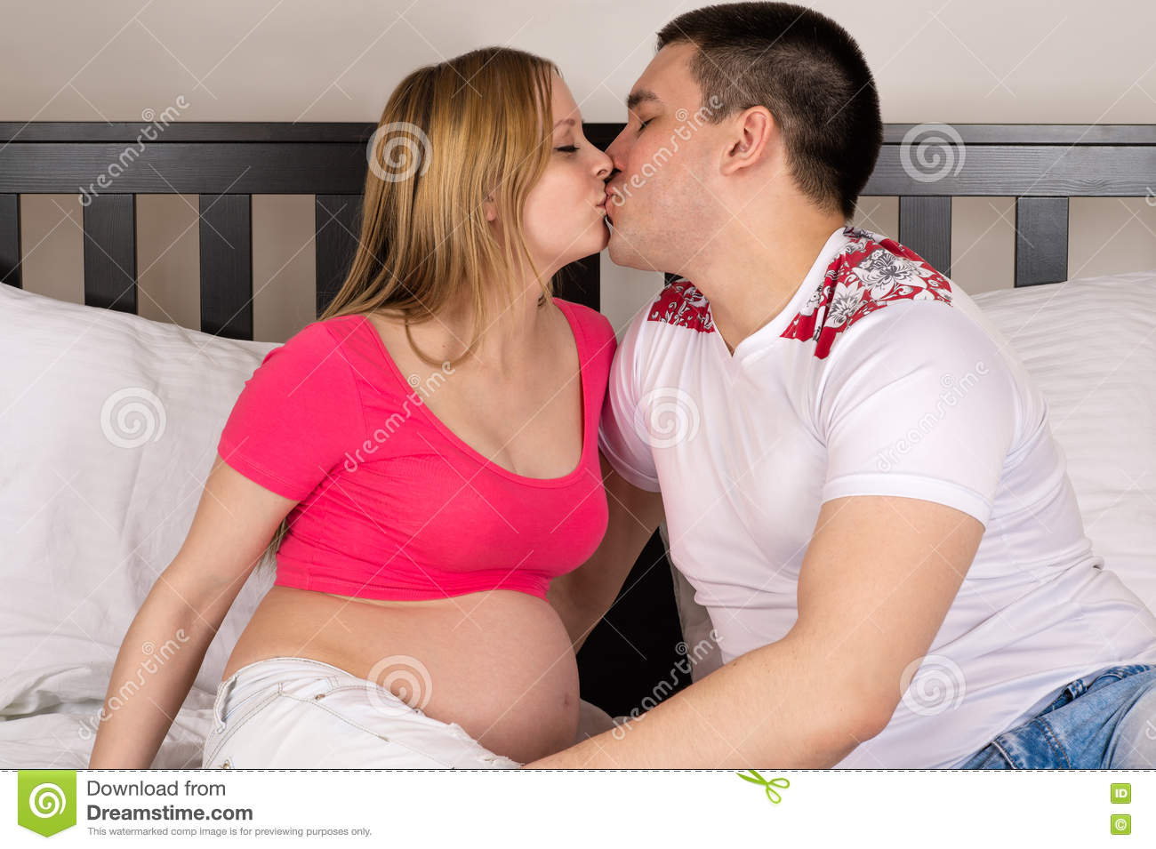 Man and woman kissing in bed