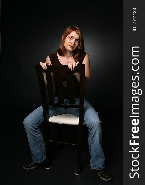 Sexy nude teen girl sitting on a chair
