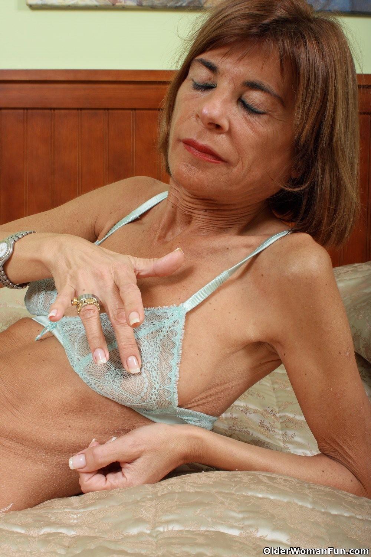 Skinny granny spreading naked